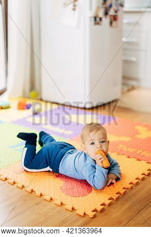 Little Baby Boy In A Blue Suit With A Carrot In His Hands Lies On His Tummy On A Colored Rug On The
