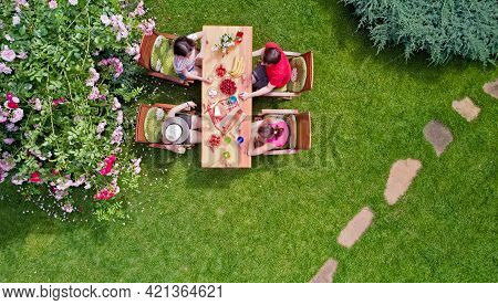 Family And Friends Eating Together Outdoors On Summer Garden Party. Aerial View Of Table With Food A