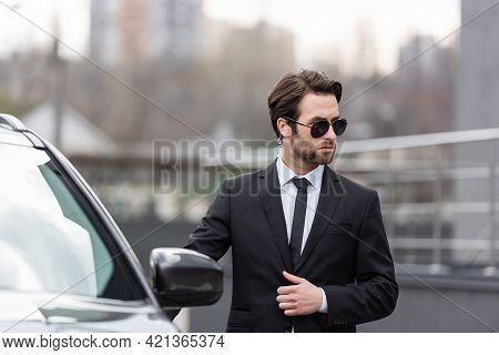 Bearded Bodyguard In Suit And Sunglasses With Security Earpiece Standing Near Modern Car.