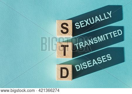 Wooden Cubes Building Word Std - Abbreviation Sexually Transmitted Diseases On Light Blue Background