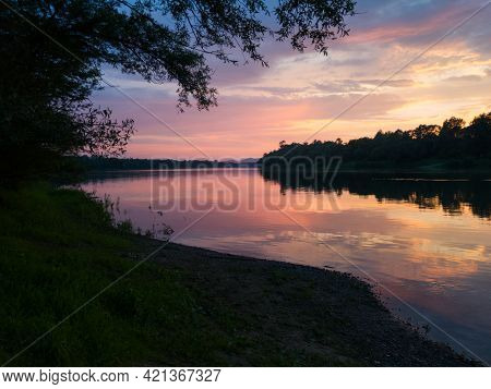 Beautiful Landscape With River, Forested Riparian Zone And Hazy Mountains In Distance During Sunset