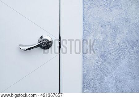 Metallic Gray Handle On A White Closed Door In An Indoor Room.