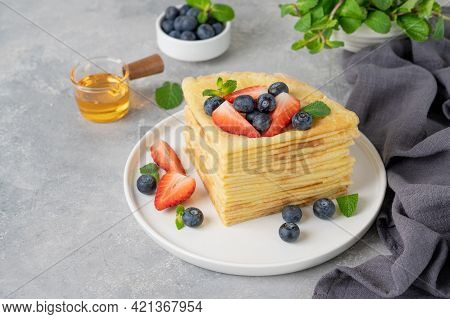 Stack Of Homemade Crepes Served With Fresh Blueberries And Strawberries On A White Plate On A Gray C