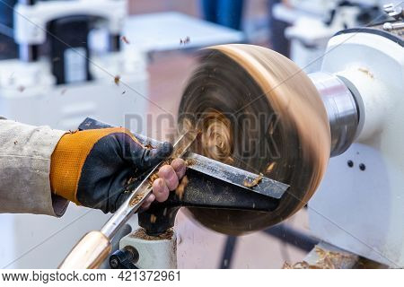 Woodworker Carving A Wooden Bowl. Carpenter With A Cutter Works On A Wooden Lathe.