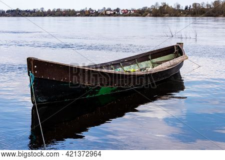 Small Weathered Wooden Fishing Row Boat At Coast On River, Housing Visible Other Side Of Coast. Brow