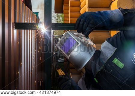 Man Welder In Welding Mask, Building Uniform And  Protective Gloves Brews Metal Welding Machine On S