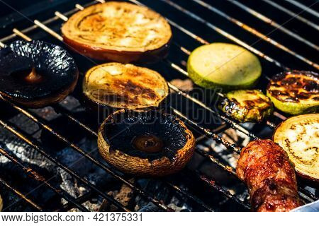 Grilling Meat Rolls Called Mici Or Mititei With Vegetables On Char Barbecue. Charcoal Grill With Bur