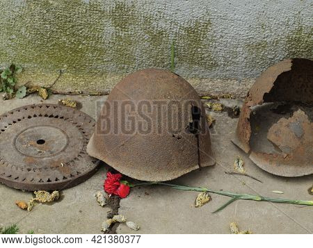 Old Soldiers' Iron Helmets With Holes Traces Of Past Battles On The Memorial To The Fallen Soldiers