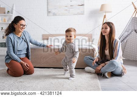 Cheerful Interracial Women Looking At Baby Boy Walking On Carpet.