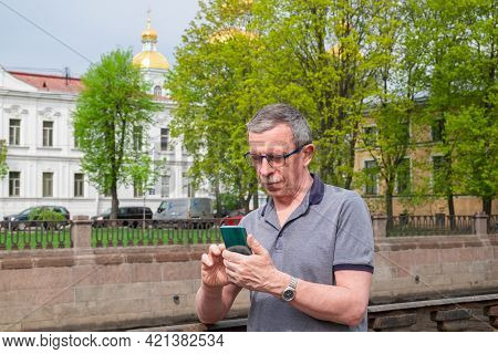 An Adult Caucasian Senior Man In A T-shirt Is Typing A Message On A Smartphone In The City In Spring