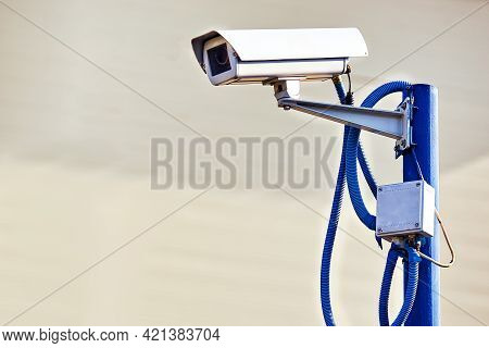 This Is A Security Camera Hanging On A Pole On A Summer Day On A Gray Background. The System Of Trac