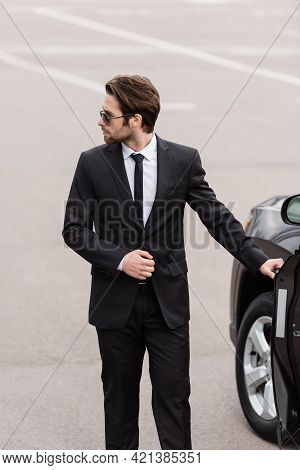 Bearded Bodyguard In Suit And Sunglasses With Security Earpiece Opening Door Of Modern Auto.