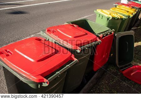 Australian Garbage Wheelie Bins With Colourful Lids For General And Green Household Waste Lined Up O