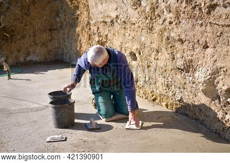 The Mason On His Knees Coats The Concrete Floor With Cement