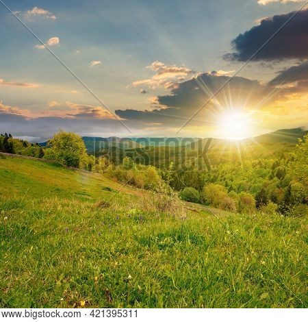 Rural Mountain Landscape In Spring At Sunset. Grass And Trees On Hills Rolling Through The Green Val