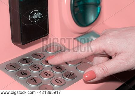 A Womans Hand Dials The Pin Code On The Banks Atm. A Young Woman Enters A Pin Code On The Atm Keyboa