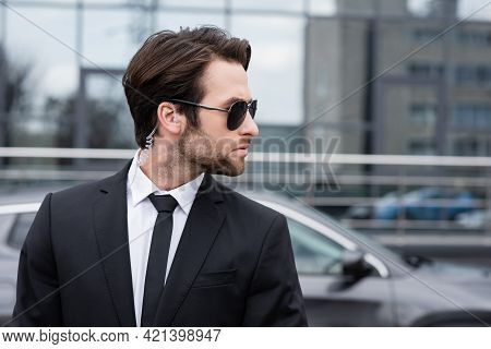 Side View Of Bearded Bodyguard In Suit And Sunglasses With Security Earpiece Near Modern Car.