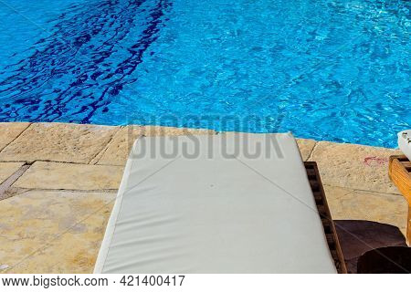 Chaise Lounge Near Swimming Pool With Clear Water