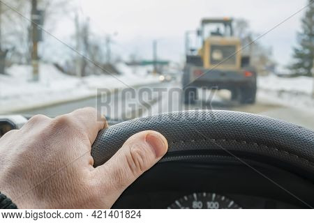The Car Driver Hand Is On The Steering Wheel Of The Car That Is Slowly Driving Behind The Tractor, G