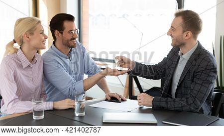 Happy Man And Woman Receiving Keys From Realtor At Meeting