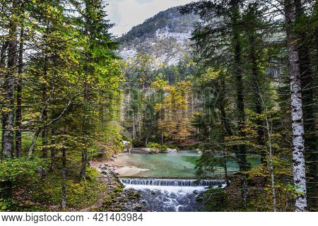 Artificial waterfall - dam. Julian Alps, Slovenia. Autumn forest in a mountain valley. Picturesque shallow lake with glacial greenish water. Light fog rises above the water.