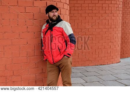 A Bearded Man Stands With His Back Against A Round Brick Wall And Looks. Hands In Jeans Pockets
