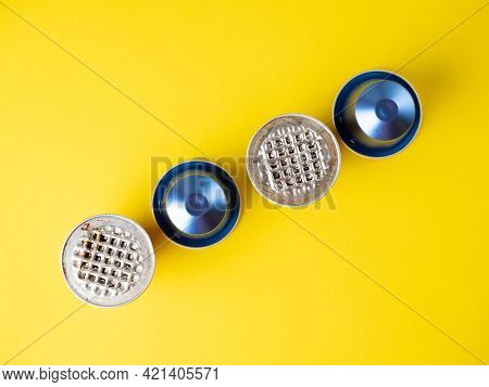 Aluminum Capsules With Ground Coffee On A Yellow Background. Several Of Them Are Used . The Concept