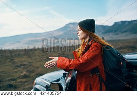 Woman In A Hat With A Backpack On Her Back Leaned On The Door Of A Car In The Mountains Outdoors