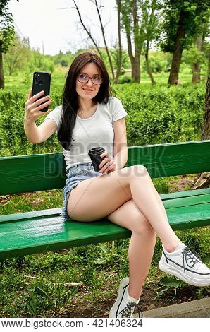 Woman Blogger Talking With Followers Or Make Selfie Looking To Smartphone Screen Sitting On Bench In