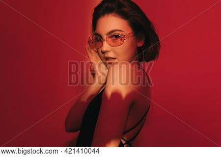 Shy Smiling Young Woman In Black Tank Top And Sunglasses Looking At Camera On Red Background.