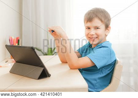 7 Years Old Child Boy Doing Lessons Sitting At Desk In His Room. Happy Kid Learning At Home Using Ta