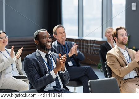 African American Businessman Applauding With Multiethnic Participants During Seminar.