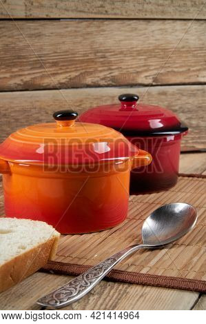 Kitchenware. Colored Ceramic Saucepans On Wooden Background
