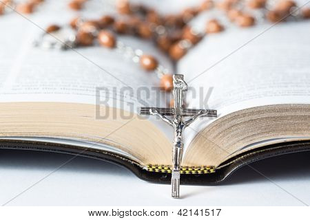 Cross of rosary beads resting against open bible