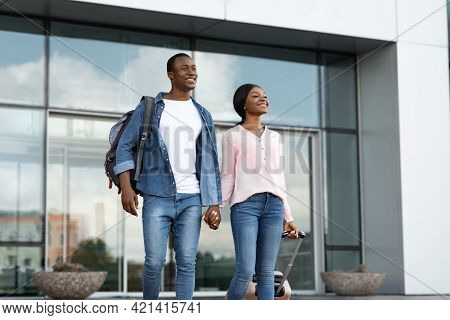 Happy Arrival. Portrait Of Cheerful Black Couple Leaving Airport Building With Luggage