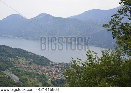 Panorama Of Mountain Lake Como With Village By Waterfront Surrounded By Green Hills Covered With Ced
