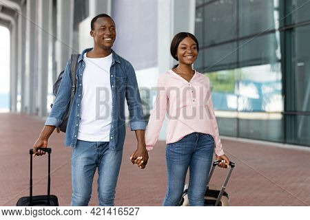 Portrait Of Cheerful Black Couple Holding Hands While Walking Near Airport Terminal