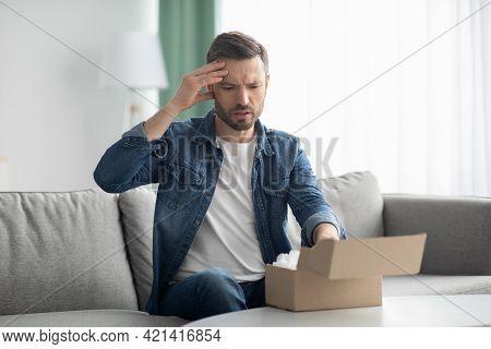 Disappointed Man Customer Checking Mail Box At Home