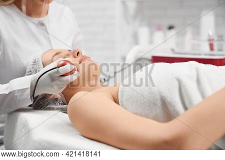 Side View Of Young Beautiful Woman Lying On Procedure For Face In Beautician. Concept Of Special Bea