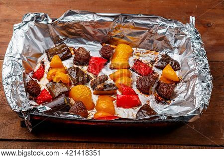 Antipasto Baked In Foil On A Wooden Table. Horizontal Photo