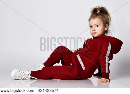 Cute Little Preschooler Girl Wearing Warm Red Tracksuit Sitting On Studio Floor Looking At The Camer