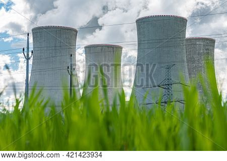 Cooling Tower Of Nuclear Power Plant Behind Green Grass. Atomic Energy. Nuclear Power And The Enviro