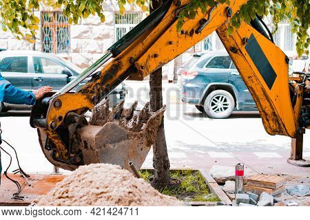 Yellow Excavator Digging The Hole On The City's Sidewalk. Heap Of Sand. Road Works On The City Stree
