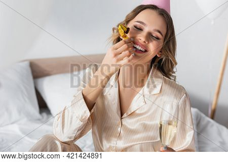 Cheerful Woman In Party Cap Holding Party Horn And Champagne.