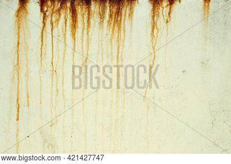 Dark Orange Streaks On A Pale Yellow Plaster Wall. Orange And Brown Streaks Of Rust Stain A Light Ye