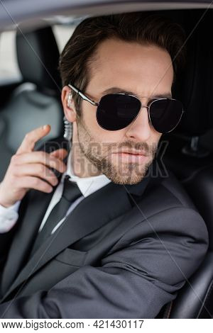 Bearded Bodyguard In Sunglasses And Suit Adjusting Security Earpiece In Car.