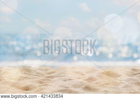 Abstract Seascape With Sand, Tropical Beach Background. Blur Bokeh Light Of Calm Sea And Sky. Summer