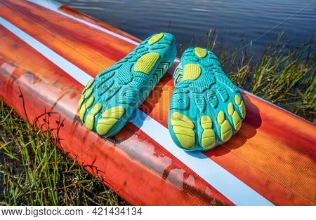 lightweight low-profile water shoes (soles up) for kayaking and other wet sports on a deck of a stand up paddleboard