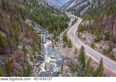 Cache la Poudre River and highway at Poudre Falls - aerial view in spring  with high flow