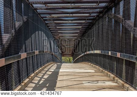 Inside Of A Modern Overhead Pedestrian Bridge Over A Highway On A Sunny Day.